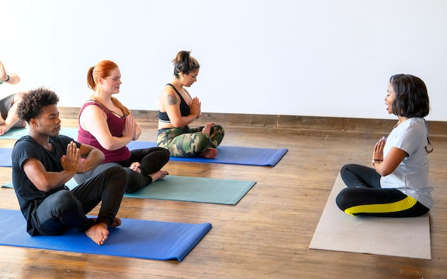Trainer and her students in a pranamasana pose