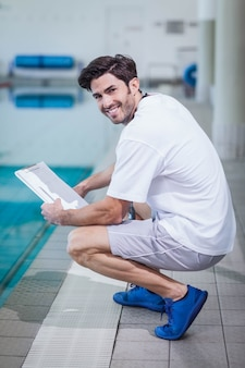Trainer holding clipboard at the pool