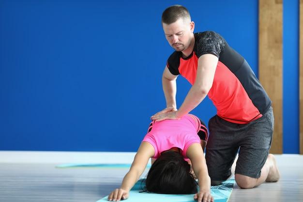 スポーツユニフォームのトレーナーがマットの上でポーズをとる女性の背中を押します。