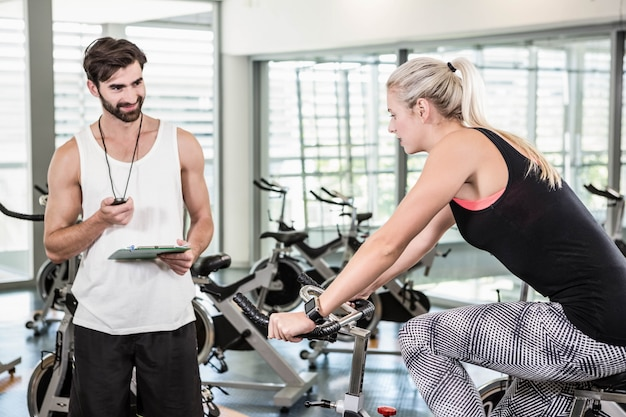 Trainer looking at stopwatch and woman using exercise bike at the gym