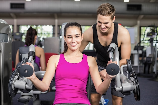 Trainer man helping athletic woman at gym