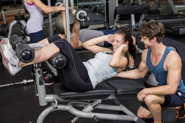 Trainer man helping woman doing her crunches in gym