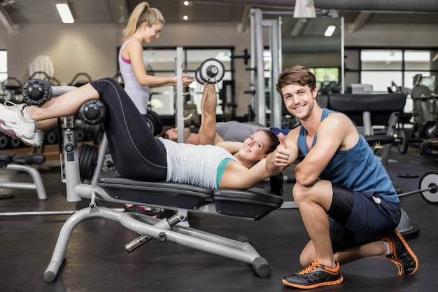 Trainer man helping woman doing her crunches and showing thumbs up in gym