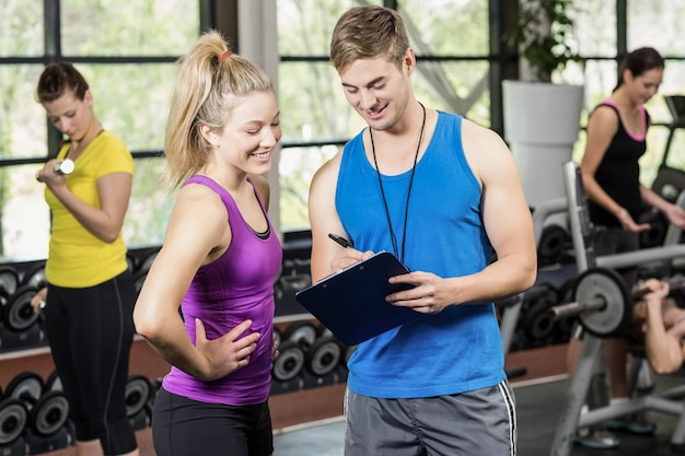 Trainer man talking with sportswoman in gym