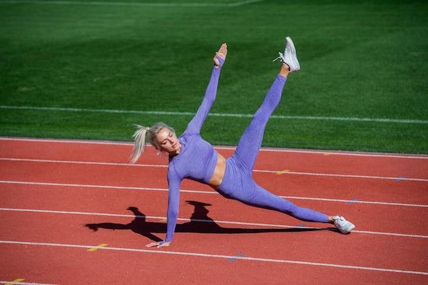 트레이너 또는 코치 교육. 완벽한 몸매. 건강하고 스포티합니다. 운동복에 섹시 한 피트 니스 여자입니다. 운동 여자는 경기장에 측면 판자에 서 있습니다. 여성 운동선수는 스포츠 운동을 할 준비가 되어 있습니다.