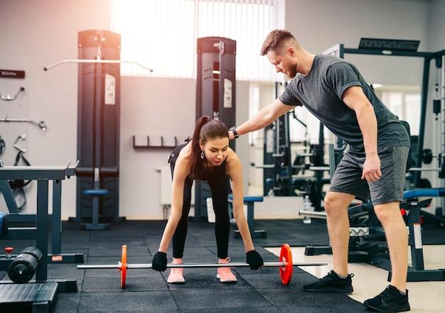 トレーナーは、女性クライアントとバーベルを使用して「スクワット」と「デスリフト」のトレーニングを練習します