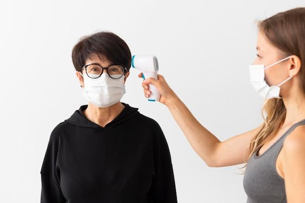Тренер, проверяющий температуру женщины