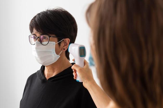 Тренер, сканирующий температуру женщины