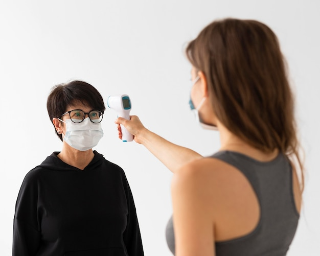Trainer scanning a woman's temperature while wearing medical masks