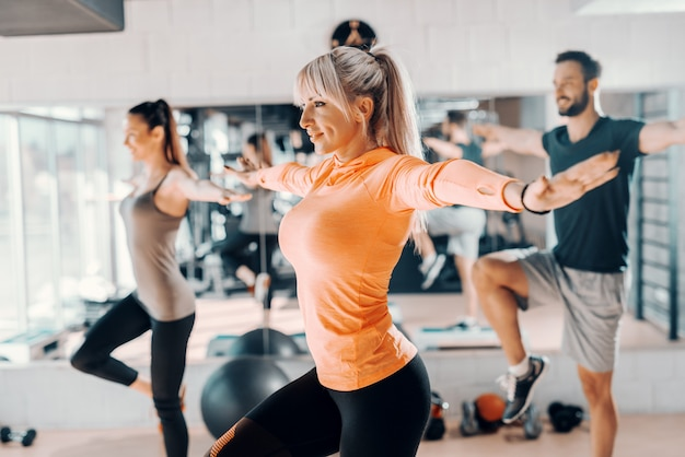 Trainer showing to the group balance exercise in gym. in background their mirror reflection. selective focus on blonde woman.