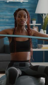아침 피트니스 작업 중에 비디오 카메라를 사용하여 온라인 요가 훈련을 기록하는 트레이너 슬림 흑인 여성.