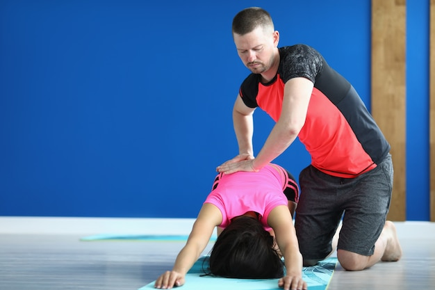 Trainer in sports uniform press on back of woman who istand in pose on mat.