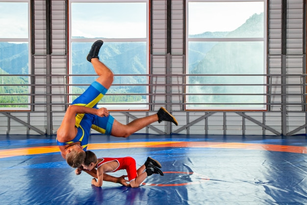A trainer in sports wrestling tights teaches a little wrestler boy