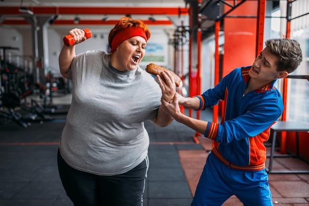 트레이너는 뚱뚱한 여자, 동기 부여, 체육관에서의 힘든 운동에서 핫도그를 가져갑니다. 칼로리 연소, 피트니스 클럽의 뚱뚱한 여성, 지방 연소, 건강에 해로운 음식에 대한 스포츠