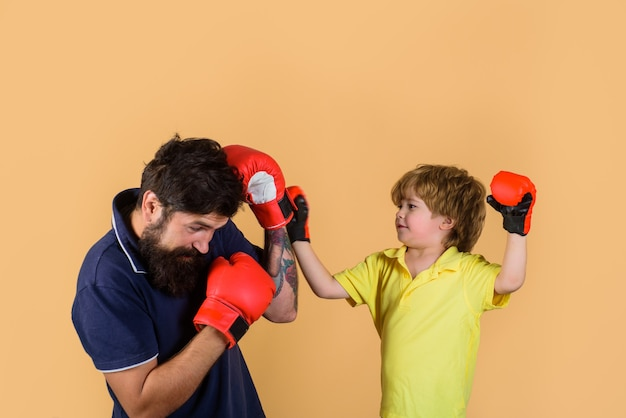 Тренер учит ребенка наносить удары по боксу, тренируя ребенка в боксерских перчатках
