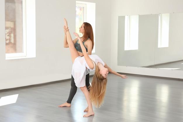 スタジオで美しい若いダンサーとトレーナー