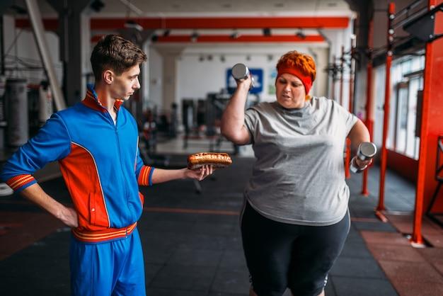 손에 핫도그가있는 트레이너는 뚱뚱한 여자가 운동, 동기 부여, 체육관에서 열심히 운동하도록 강요합니다. 칼로리 연소, 피트니스 클럽의 뚱뚱한 여성, 지방 연소, 건강에 해로운 음식에 대한 스포츠