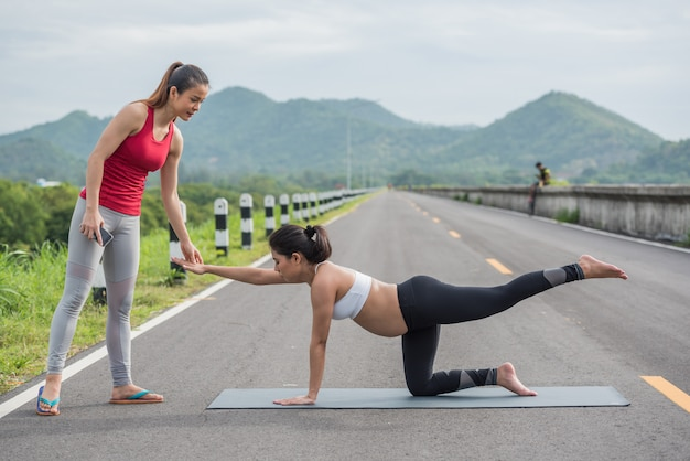Trainer with pregnant woman doing yoga outside.