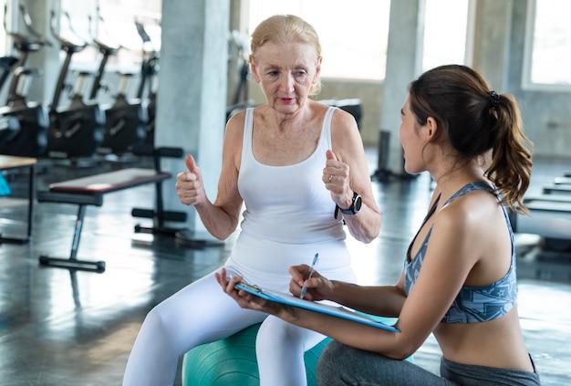 체육관에서 수석 여자 운동 트레이너입니다. 노인의 건강한 생활 방식과 운동 개념