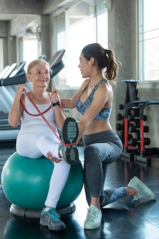 체육관에서 운동을 스트레칭 수석 여자와 트레이너입니다. 노인의 건강한 생활 방식과 운동 개념.