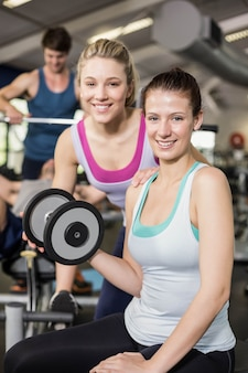 Trainer woman helping woman lifting dumbbell at gym