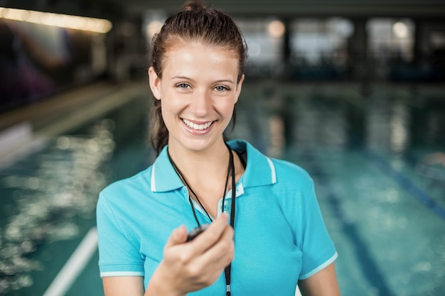 Trainer woman holding a stopwatch on poolside