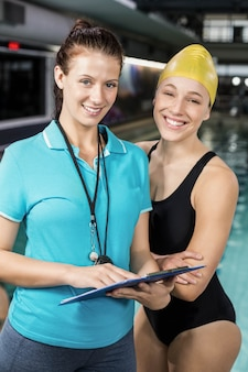 Trainer woman showing clipboard at a swimmer at the pool