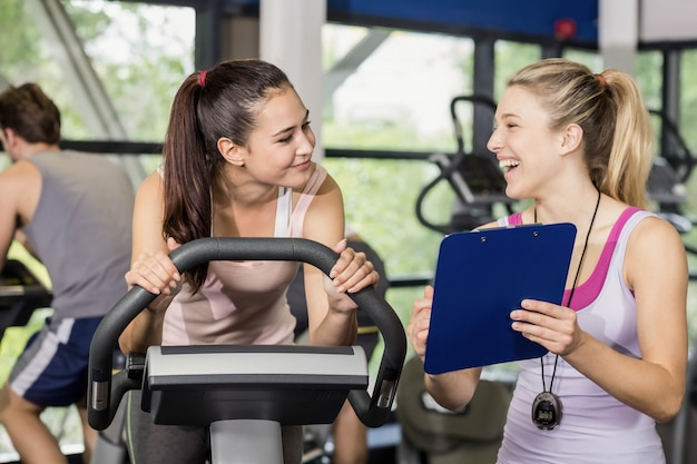 Trainer woman talking with a woman doing exercise bike at gym