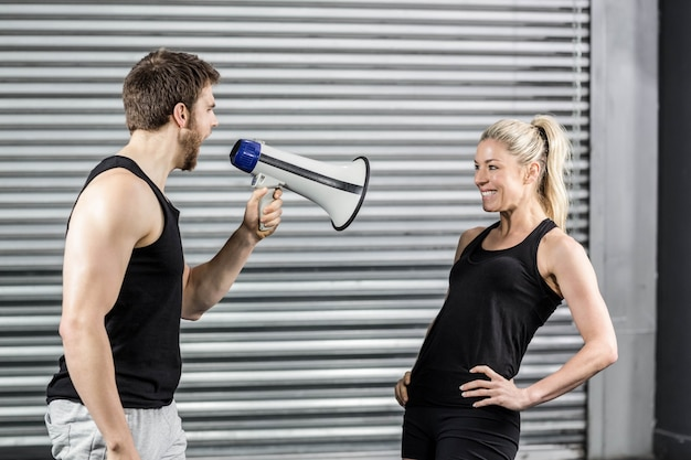 Trainer yelling through the megaphone at crossfit gym