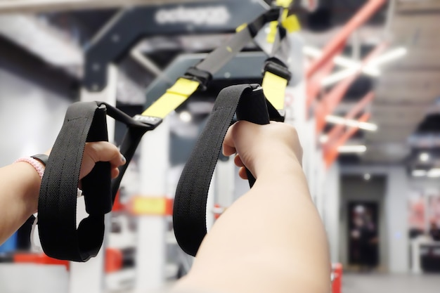 Training arms with trx fitness straps in sport club or gym and fitness room.