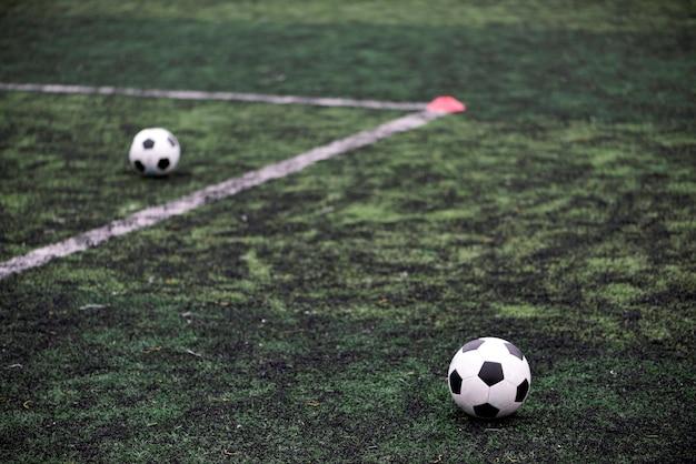 Training balls in green soccer field