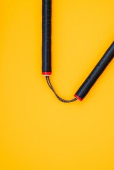 Тренировочный черный нунчаку изолирован на оранжевой поверхности