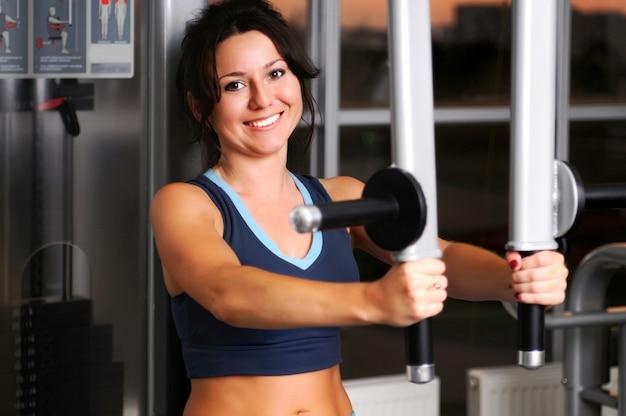 Тренировка кавказской белой брюнетки делает упражнения для мышц рук на фитнес-оборудовании