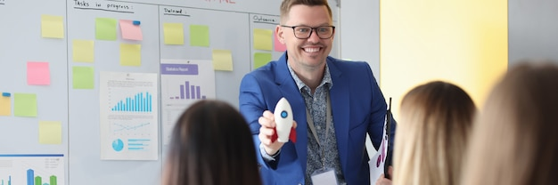 Training coach holds rocket in his hand and conducts conference. business forums for start-up development concept