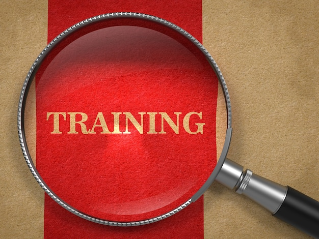 Training concept. magnifying glass on old paper with red vertical line background.