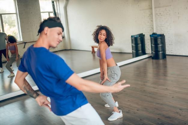훈련 일. 좋은 분위기의 거울 근처에서 춤을 추는 검은 곱슬 머리를 가진 머리띠와 소녀의 젊은 남자