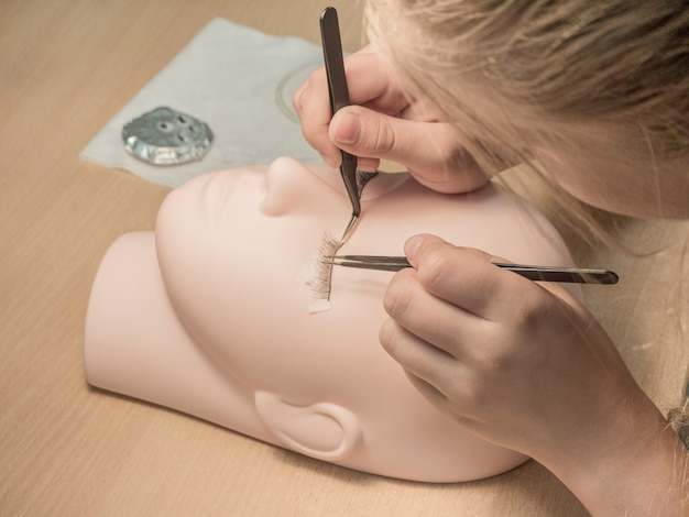 Training eyelash extensions. work on coloring eyelashes on a mannequin.