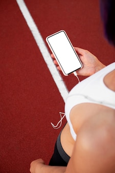 Training and fitness in the stadium. runner girl holds smartphone using touch screen to select music or text on app before launching on track. female athlete legs and feet close-up with white sneakers