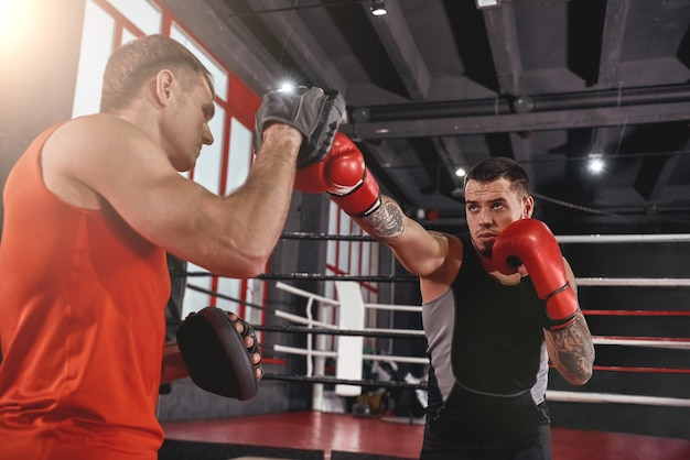 大切な日のトレーニング。黒のボクシングジムのパートナーとボクシングの足のスポーツ服のトレーニングで筋肉アスリート入れ墨男