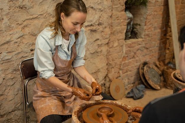 Обучение работе на гончарном круге мужчина и женщина работают вместе с глиной
