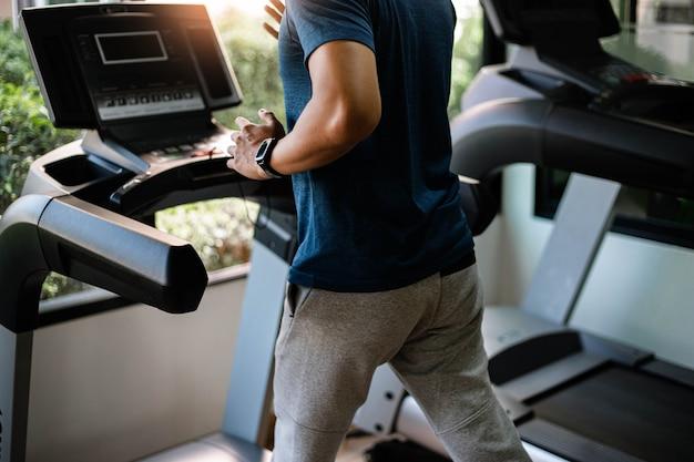 トレーニングジムのコンセプトは、健康的なルーチンとしてジムのサイクリングマシンで有酸素運動をしている10代の男性です。