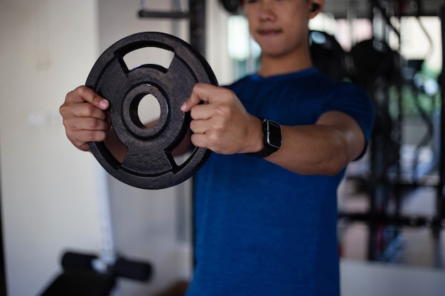 トレーニングジムのコンセプトは、重い鉄の車輪を持って両手を使って筋肉質の男性のティーンエイジャーです。