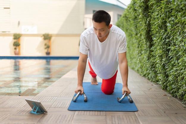 トレーニングジムのコンセプトは、covid-19パンデミックの最中にラップトップでソーシャルメディアにアクセスしながら運動をしている若い男性の大人です。