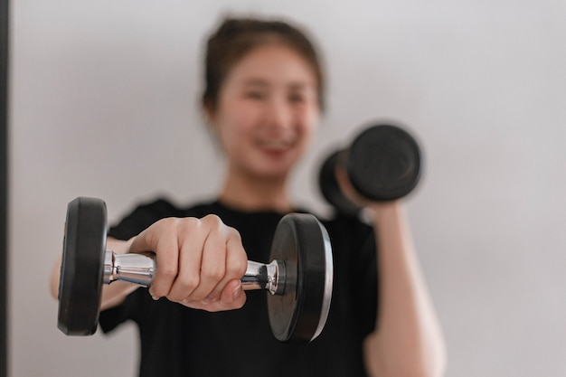 Training gym concept a female teenager using her  arm lifting a dumbbell upward and downward in the gym.