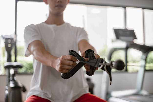 Training gym concept a male teenager using a gym equipment pulling his both muscular arms against the machine.