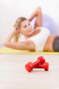 그녀의 복근 훈련. 전경에 누워 아령으로 매트에서 운동하는 성숙한 여자