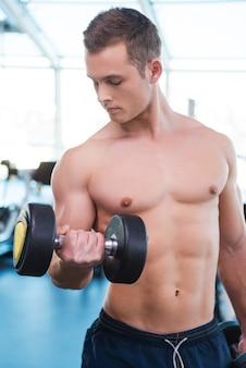 彼の筋肉を訓練します。ジムに立っている間ダンベルでトレーニングする自信のある若い筋肉の男