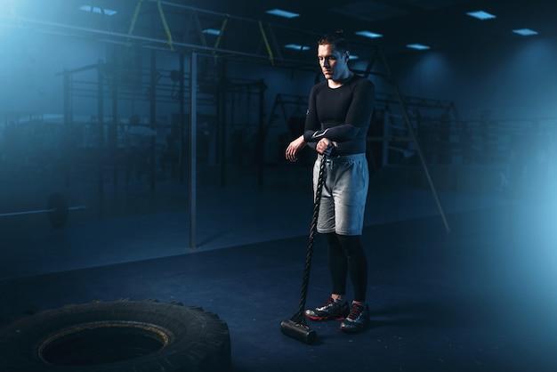 Тренировка в тренажерном зале, человек с кувалдой бьет шину
