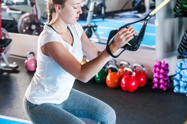 Тренировки в спортзале. девушка фитнеса для наращивания мышц. фитнес-тренер для разминки. горизонтальное фото