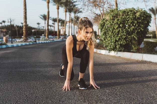 通りを走る準備をしてうれしそうな美しい女性の晴れた朝のトレーニング。夏、強いスポーツウーマン、エネルギー、モチベーション、健康的なライフスタイル、トレーニング、幸福